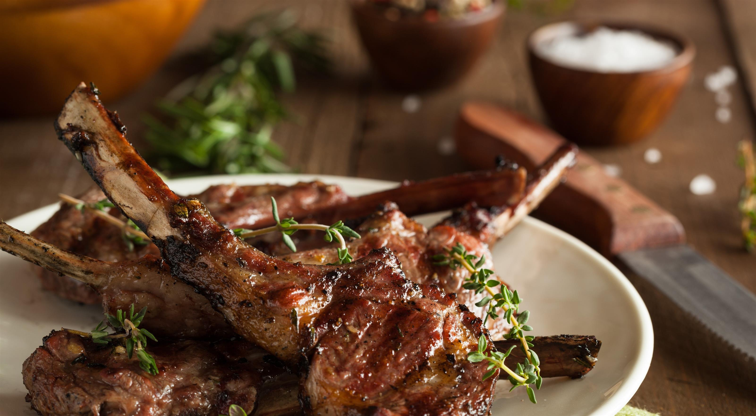 cooked lamb chops on a plate with fresh herbs