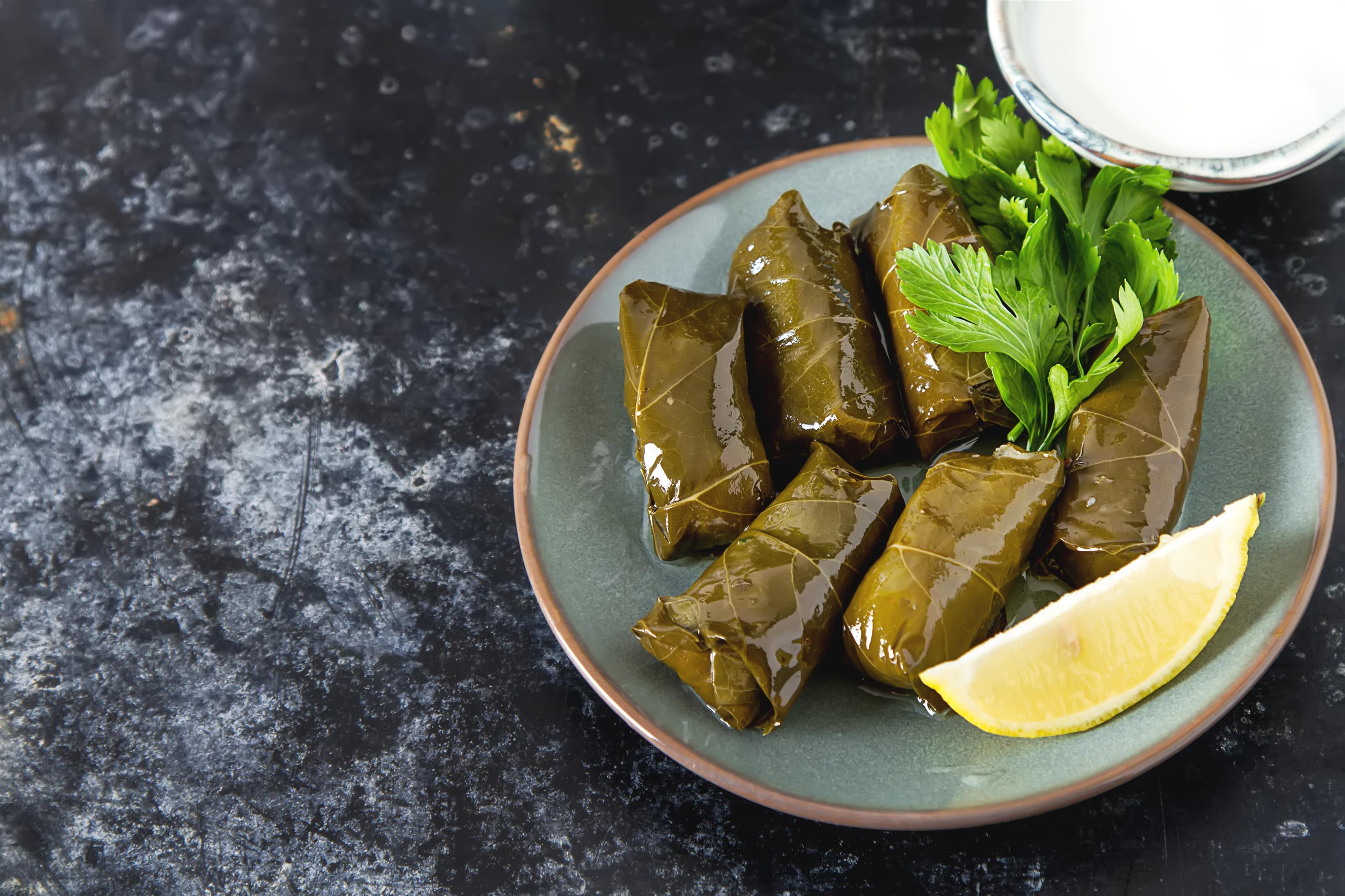 stuffed grape leaves on a plate with herbs and lemon slice