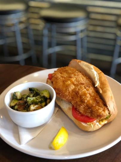 fried fish sandwich with vegetable side