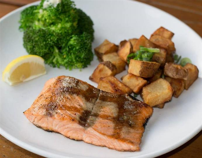 glazed cooked salmon with pottaoes and vegetables