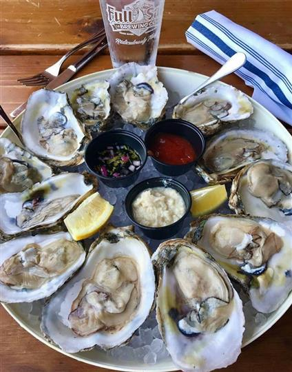 oysters on the half shell in a bucket full of ice with dipping sauces