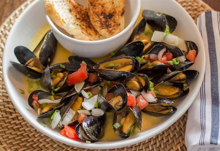 cooked mussels in a bowl with garlic bread
