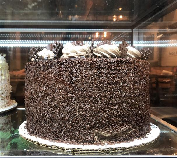 chocolate cake being held by an employee with a slice already taking from it