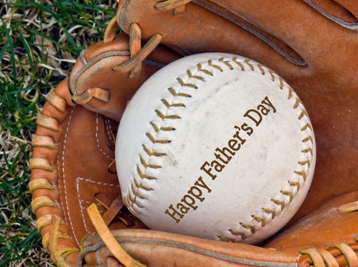 A soft ball in a glove that says happy fathers day
