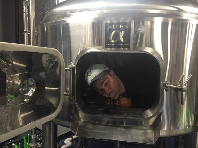brewing process showcasing with a brewmaster inside one of the metal containers goofing off