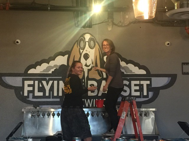 two employees setting up the flying basset brewing sign