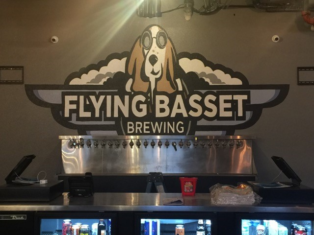 bar area showing  the bar in front of the flying basset brewing sign