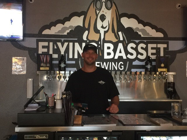 bartender smiling behind the bar in front of the flying basset brewing sign