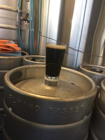 stout filled pint glass sitting on top of a beer keg