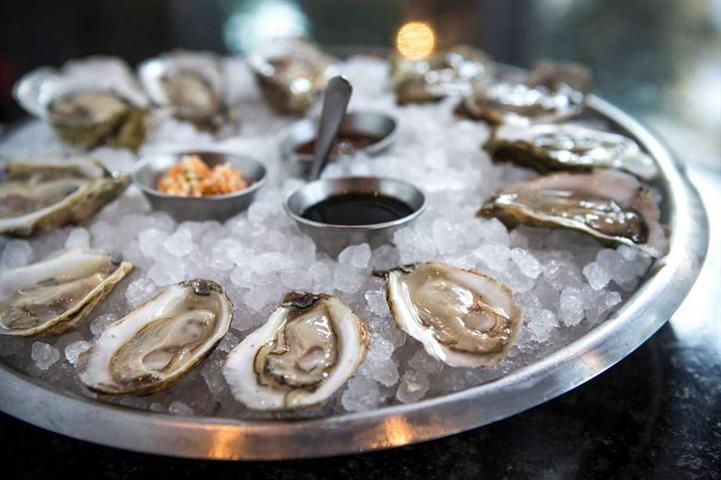 oysters on the half shell on ice with dipping sauces