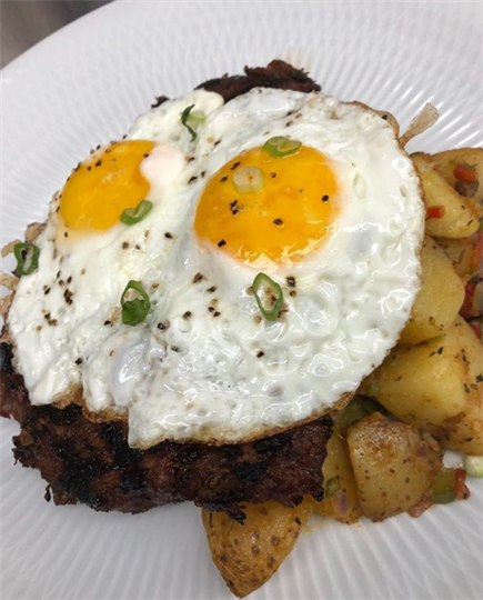 two fried eggs over a tseak with a side of potatoes