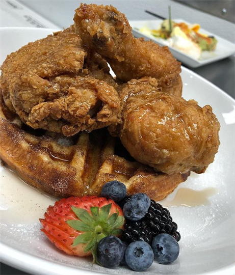fried chicken and waffles covered in syrup with fruit