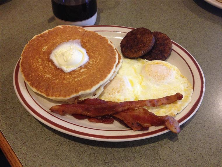 Pancakes with melting butter, two eggs, bacon, sausage patties on dish on gray table
