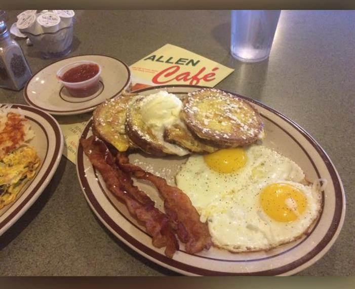 Two eggs, bacon, pancakes on dish on gray table.