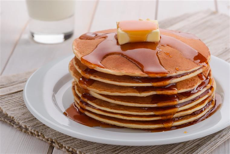 Stacked pancakes with butter and syrup on white dish