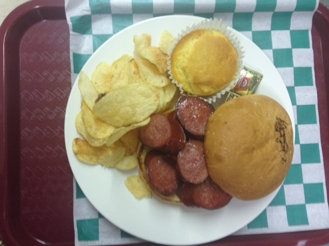 smoked sausage on a hamburger bun with potato chips and a corn muffin