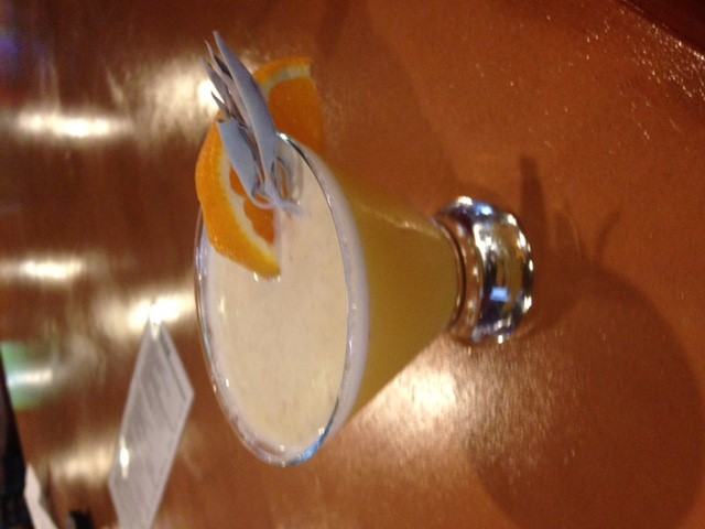 mixed cocktail with an orange wedge