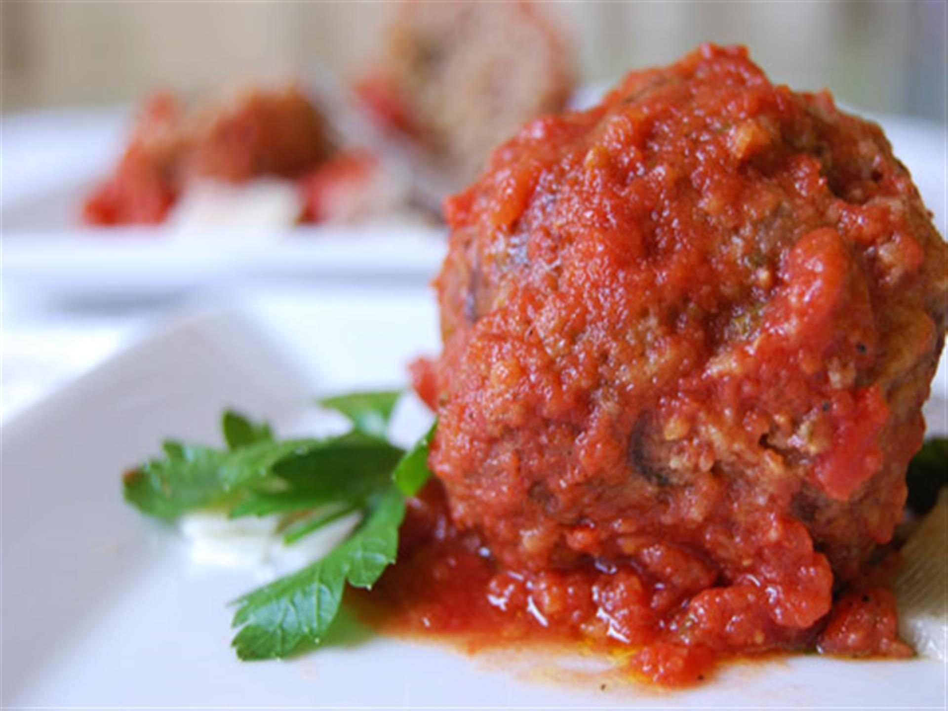 One meatball with sauce poured on top of it