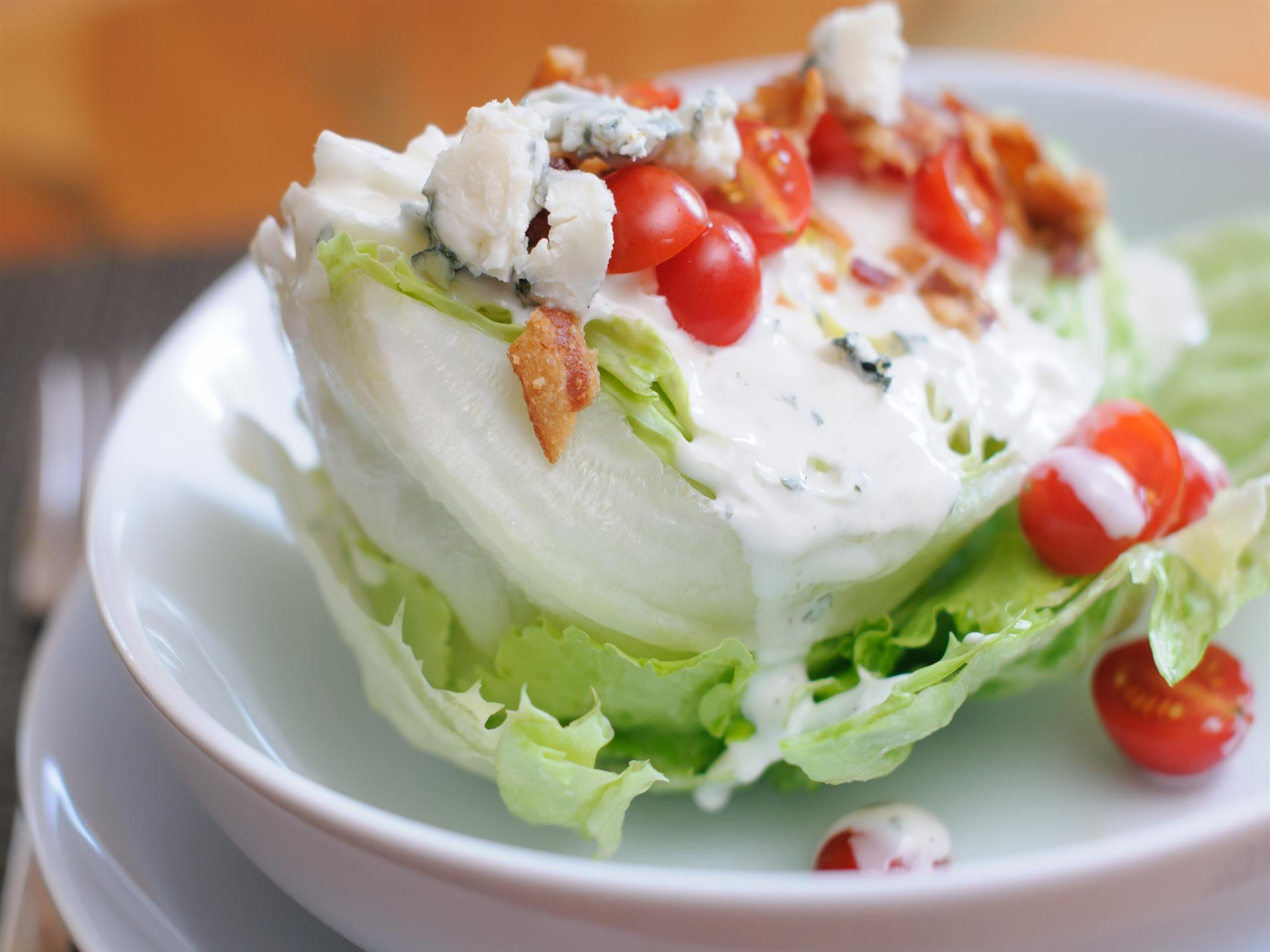 Wedge salad with an ice berg wedge,tomatoes, bleu cheese, and bacon on top