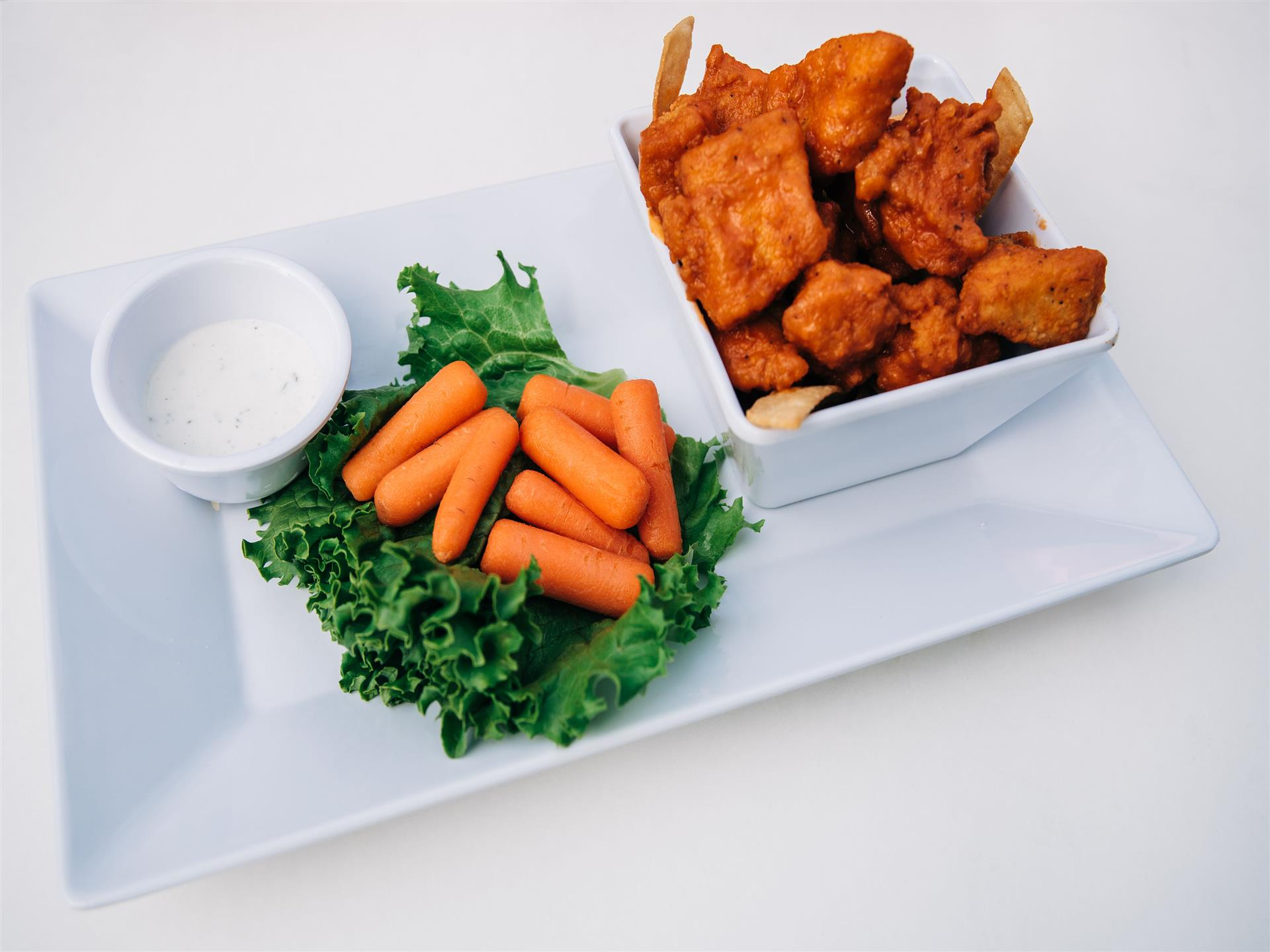 Fried seafood served with a side of carrots and dipping sauce