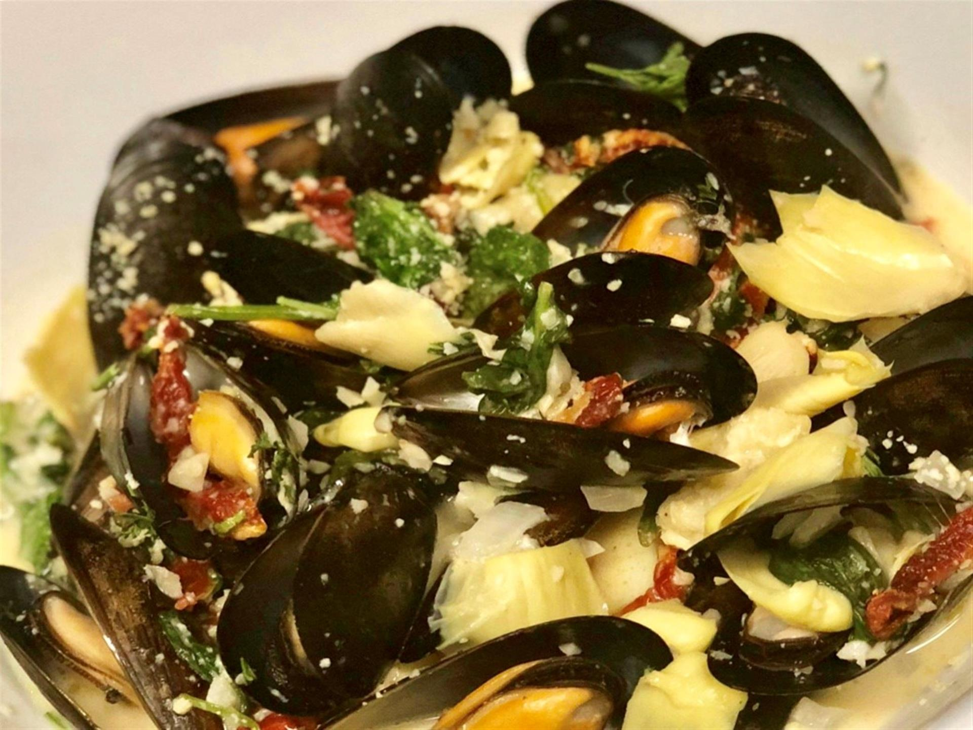 Mussels Sautéed In A Lemon Herb Wine Sauce With Artichoke Hearts, And Sun-Dried Tomatoes