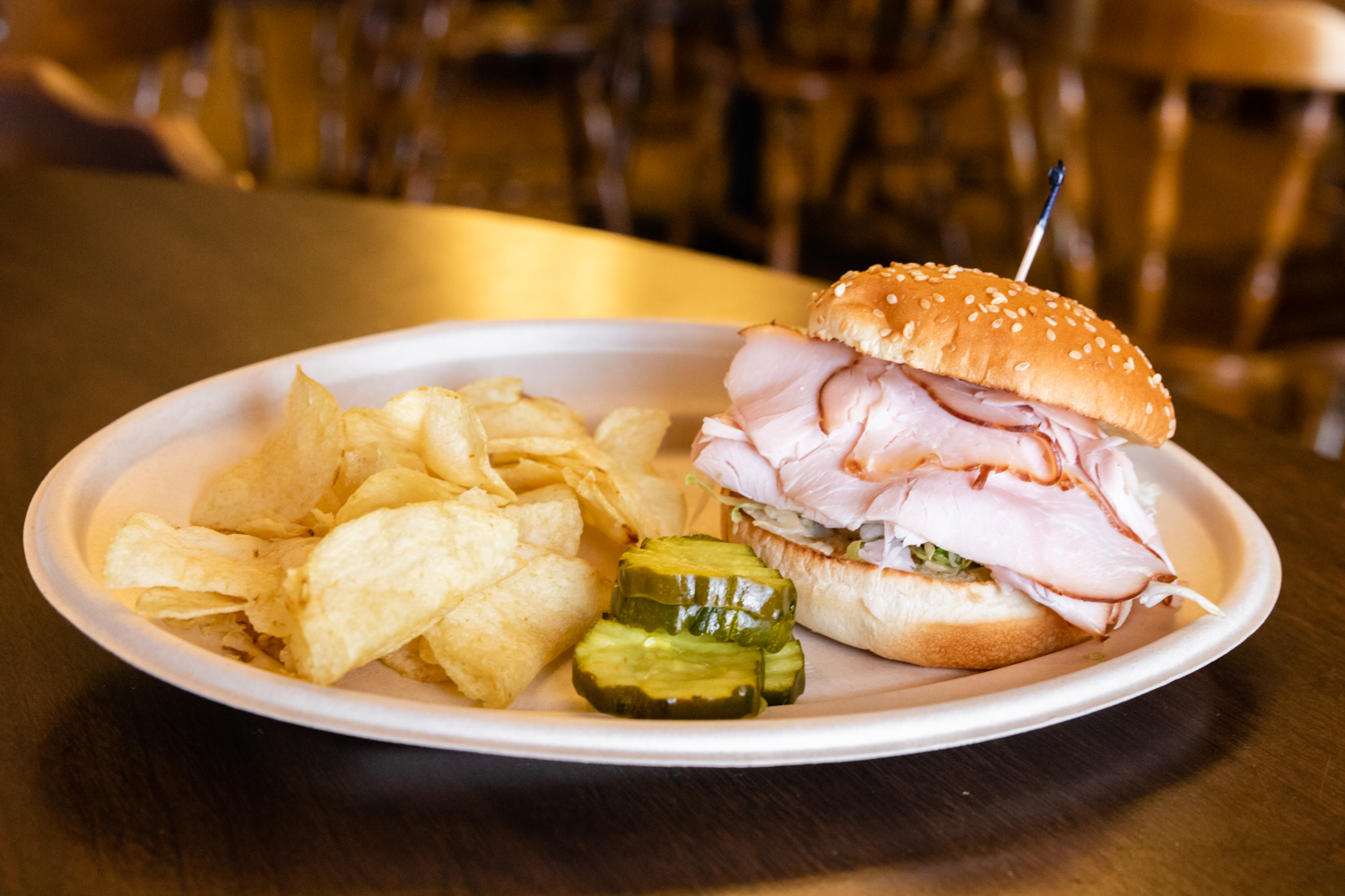 Turkey sandwich with side of chips and pickle on white dish