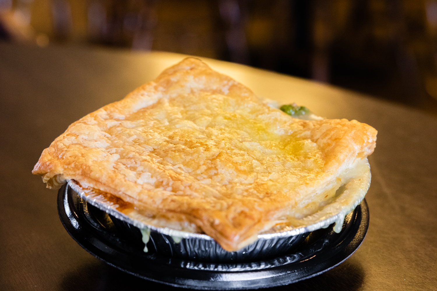 Turkey pot pie in aluminum foil dish on top of black dish