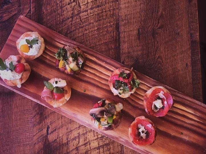 small appetizers on a wooden board with herbs