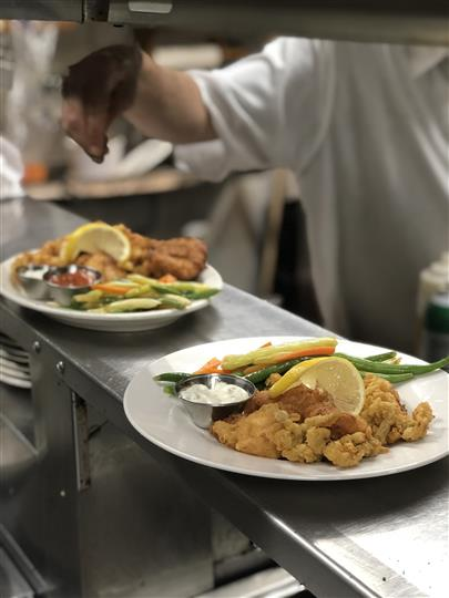 Two fried dishes on kitchen counter