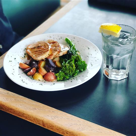 Grilled chicken served with veggies and a glass of water
