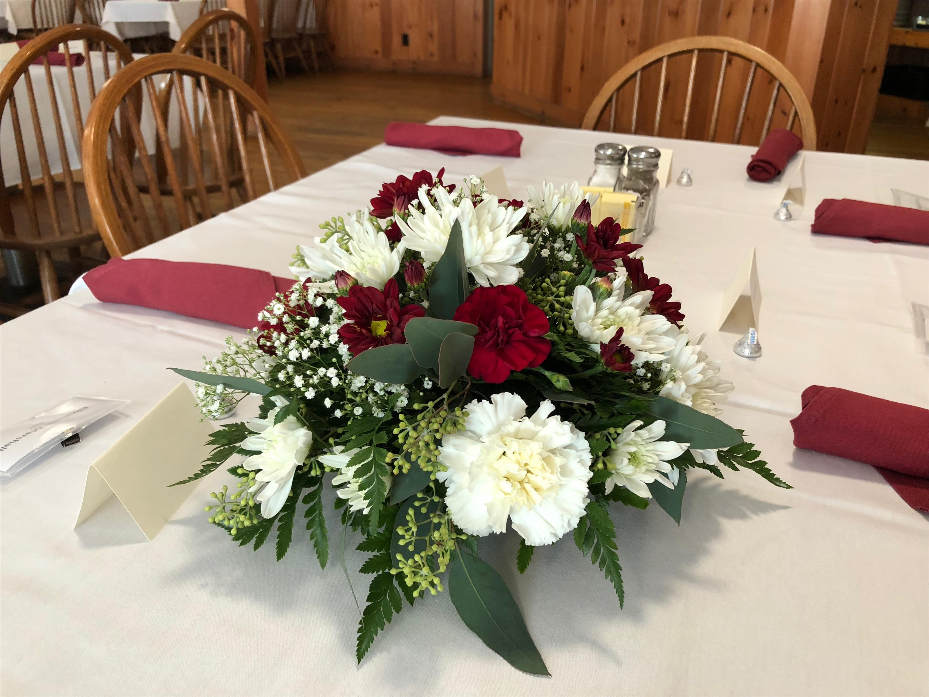 A flower centerpiece on a table set