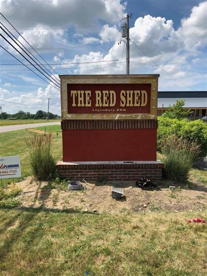 "Road sign of the restaurant right by the street that writes ""The Red Shed"""