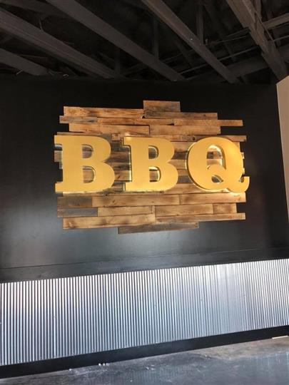 Mounted sign on the wall with the letters BBQ against a wooden background