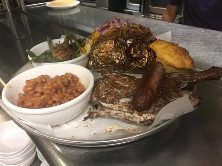 Meat platter served with baked potato, beans, collard greens  and corn bread on the side