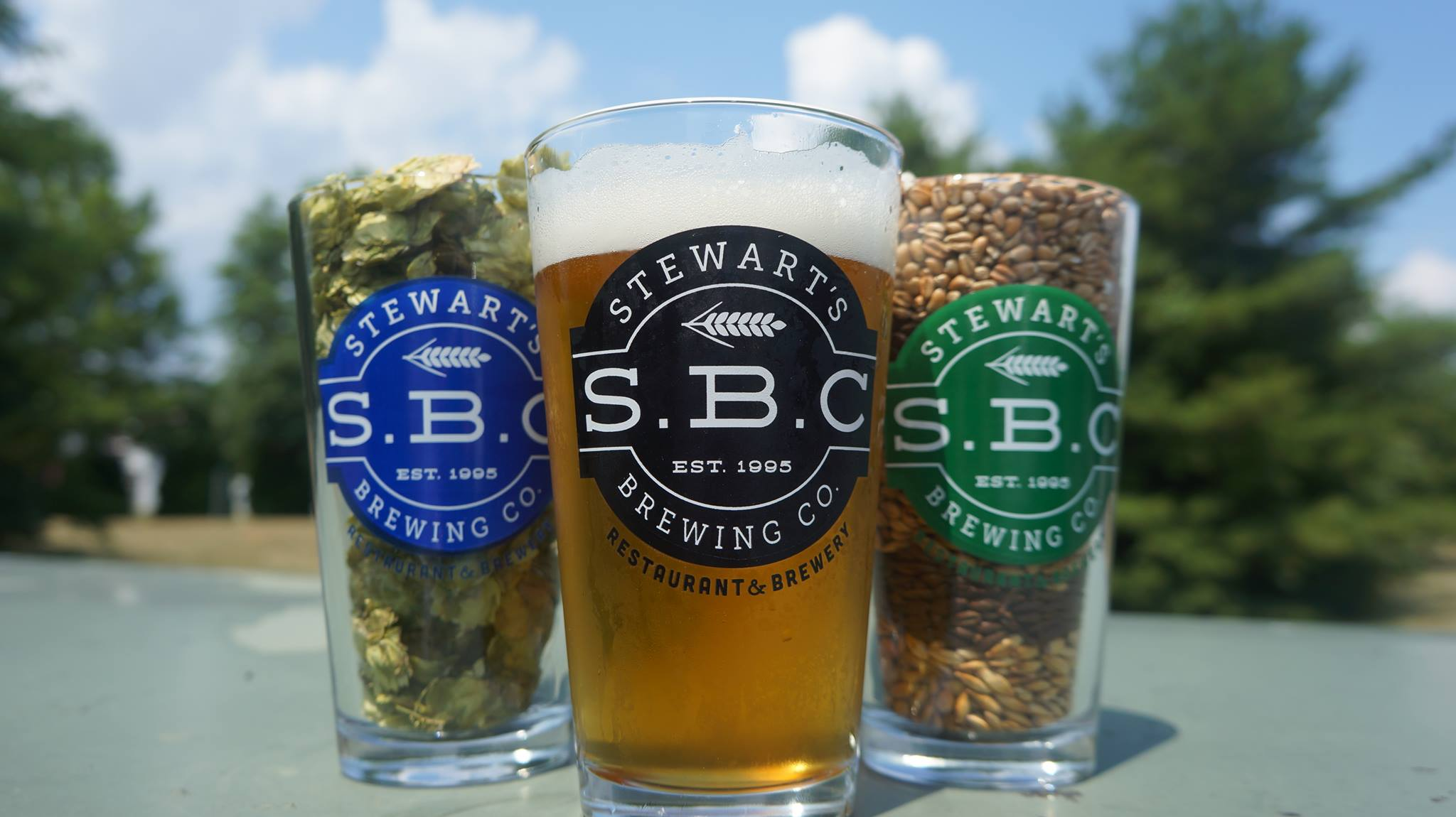 S.B.C. Logo on a pint of lite beer in the center with a pint of hops and pint of wheat to each side