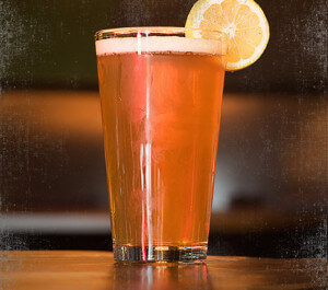 light beer filled pint glass with lemon wedge