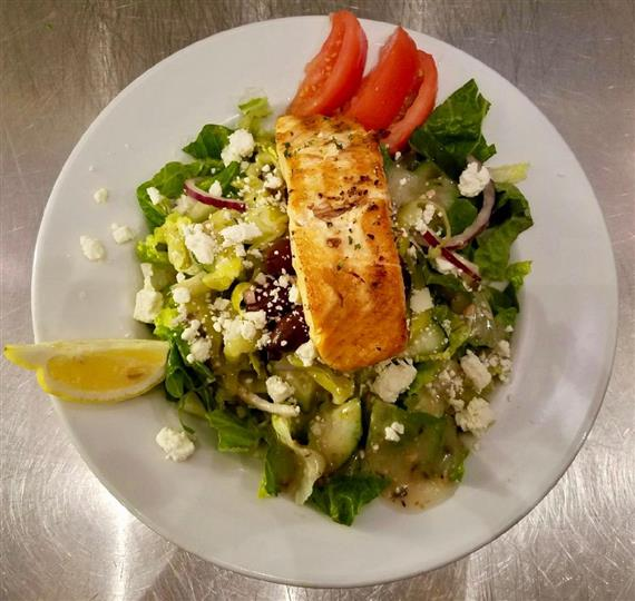 Grilled salmon salad with tomatoes, crumbled cheese, tomatoes, onions, cucumbers.