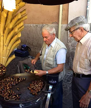 Man roasting chestnuts with interested onlooker