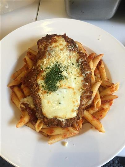 Veal cutlet parmigiana. Hand-breaded veal cutlet baked with mozzarella over a bed of pasta marinara.