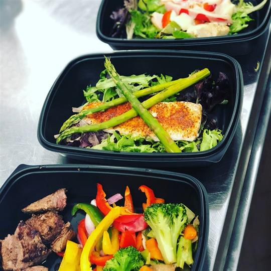Assorted containers with steak, chicken, lettuce, asparagus, broccoli, peppers