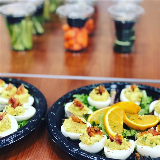 Plates of deviled eggs with orange slices.