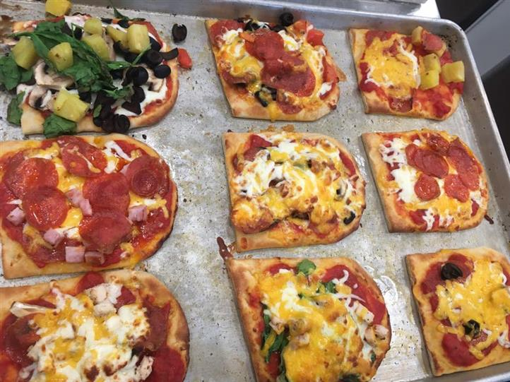 Variety of finished pizzas on baking sheet
