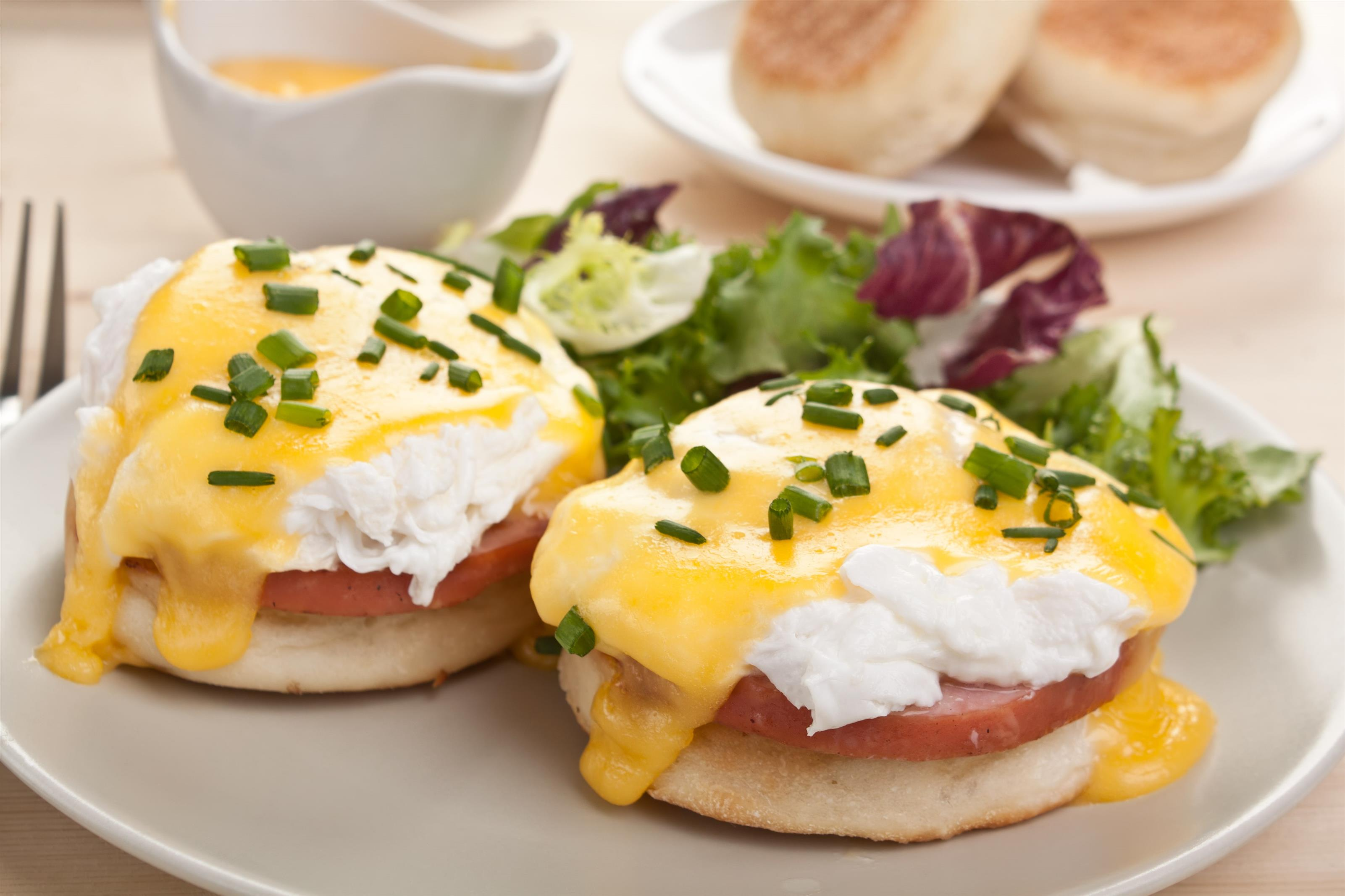 Eggs benedicts on dish with side of lettuce, rolls