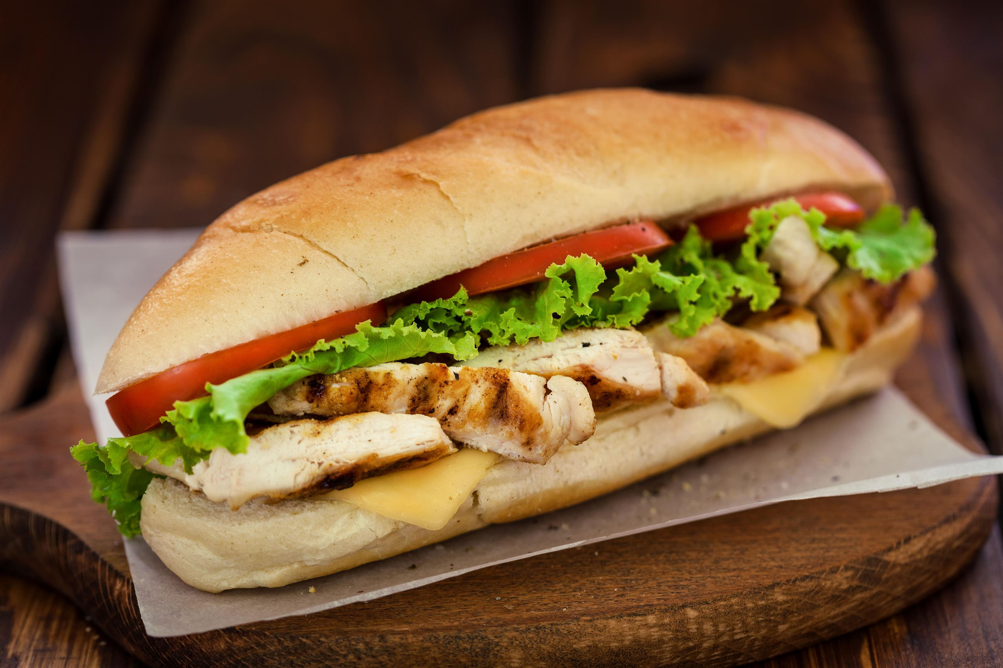 Chicken sandwich with romaine lettuce, cheddar cheese, tomatoes, ranch dressing.