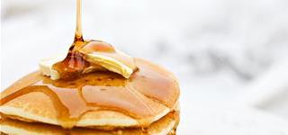 Stack of pancakes and butter with syrup being drizzled on