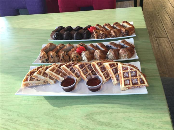 Assorted pastries and waffle pieces laid out on dishes