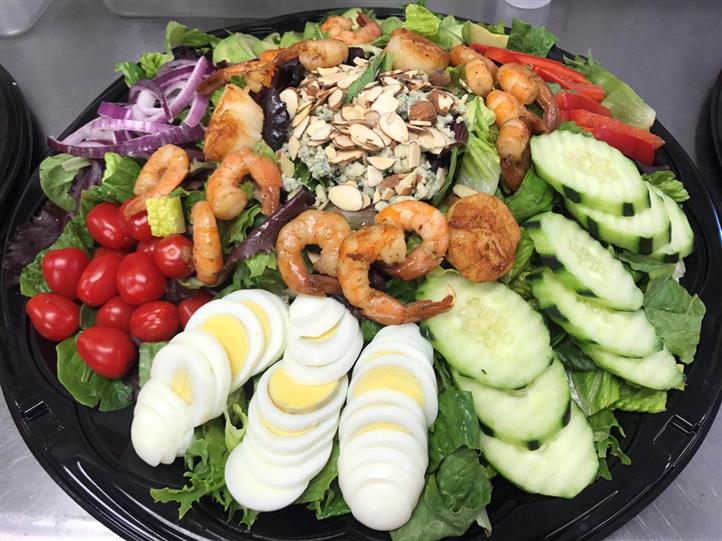 Shrimp, avocado, lettuce, onions, eggs, cucumbers, tomatoes, peppers, almond slivers on catering dish