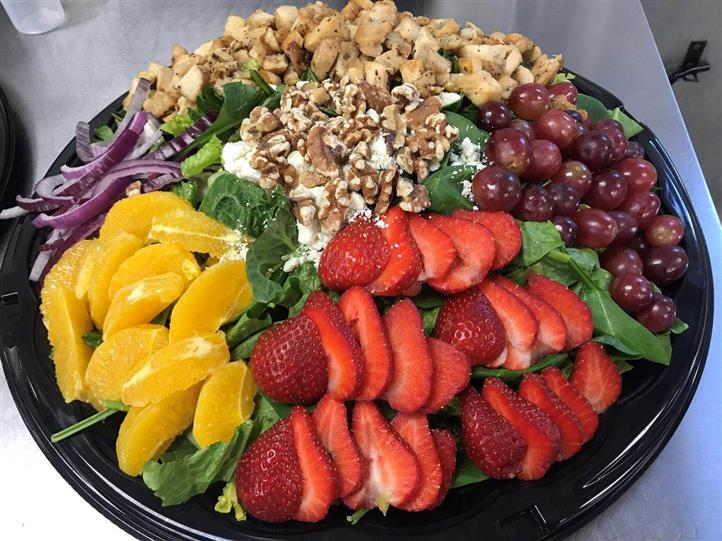Strawberries, grapes, oranges, walnuts, onion, chicken on catering platter.