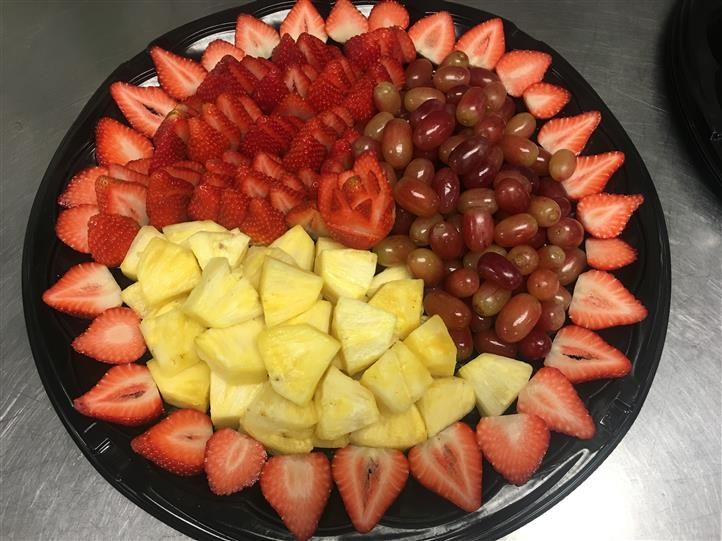 Decorative fruit platter with strawberries, red grapes, pineapple
