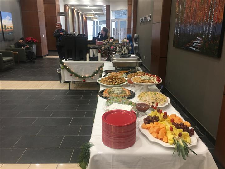 Variety of small wraps and fruit platter on table during holiday event